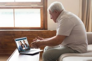 man sitting on couch and watching family over video conference